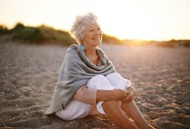 stock photo of retirement age  - Happy retired woman wearing shawl sitting relaxed on sand at the beach - JPG