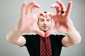 Portrait of a man makes the heart using fingers on gray background