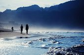 Silhouette of the people walking on the sand, amazing dark silhouette of mountains around bay