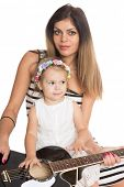 Smiling mother with her �?�¢??�?�¢??daughter and two years old with the guitar.