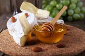 Camembert cheese on paper, grapes, nuts and honey in glass bowl on on cutting board on wooden background