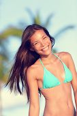 Bikini beach woman happy smiling laughing lifestyle. Bikini girl wearing looking at camera excited and joyful. Beautiful sexy mixed race woman having fun on summer travel vacation.