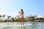 Hawaii beach lifestyle woman paddleboarding in bikini.on SUP. Beautiful multiethnic woman surfing on stand up paddleboard on Big Island, Hawaii. Multiracial Asian Caucasian girl.