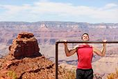 Fitness athlete man training pull ups in amazing nature landscape of Grand Canyon. Strength training fit male working out exercising outdoors in summer doing pull-ups and chin-ups.