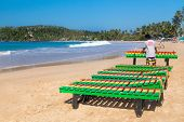 UNAWATUNA, SRI LANKA - MARCH 6, 2014: Local worker putting colourful wooden deck chairs on beach.  Unawatuna is a major tourist attraction in Sri Lanka  famous for its beautiful beach and corals.