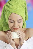 Woman in bathrobe with face cream