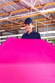 cheerful young textile factory worker holding large pink fabric