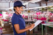 stock photo of production  - young female african textile factory worker in production area - JPG
