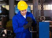 manual factory worker adjusting machine
