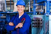 cheerful young industrial technician looking at the camera