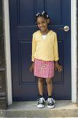 African girl standing in front of door