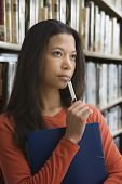 Mixed race woman thinking in library