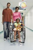 African girl smiling in wheelchair with parents in hospital