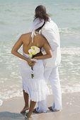 Multi-ethnic bride and groom at beach