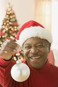 African man wearing Santa hat and holding Christmas ornament