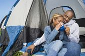 African couple drinking coffee at campsite