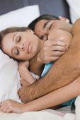 Hispanic couple sleeping in bed