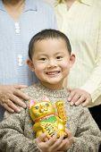Chinese boy holding beckoning cat