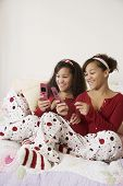 picture of identical twin girls  - African twin sisters looking at cell phones - JPG