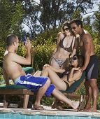 stock photo of pacific islander ethnicity  - Pacific Islander man taking photograph of friends - JPG