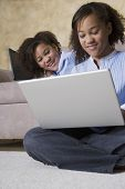 African twin sisters looking at laptop