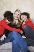Multi-ethnic mother and twin daughters hugging