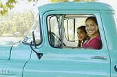 Hispanic mother and daughter driving truck