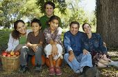 Multi-ethnic family sitting under tree