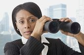 African businesswoman holding binoculars