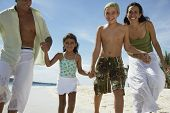Hispanic family holding hands at beach