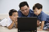 Asian father and sons looking at laptop