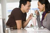 Asian couple sharing milkshake