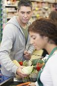 Hispanic man checking out at grocery store