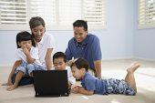 Asian family looking at laptop