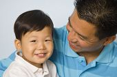 Asian father smiling at son