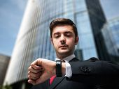 Young businessman looking at his watch