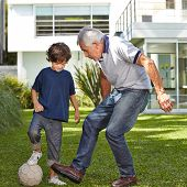 Boy playing soccer with his grandfather in garden in front of a house