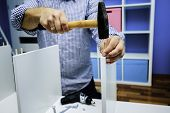 DIY, man stabs wooden dowel with a hammer