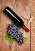 Red wine bottle and bunch of red grapes on wooden table background