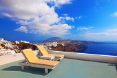 Two deckchairs on the roof of the building on Santorini island, Greece. View on Caldera and Aegean s