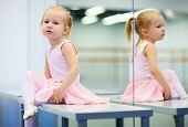 stock photo of leotard  - Adorable little ballerina wearing pink leotard in dancing school - JPG