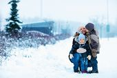 Young mother with two kids outdoors on beautiful winter day with snow