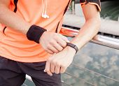 Close up of active guy using fitness device