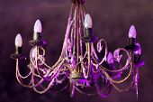 Retro chandelier with soft purple light.