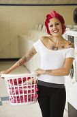 Tattooed Hispanic woman holding laundry basket