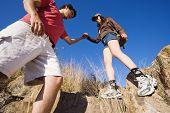 Hispanic man helping girlfriend on rocky hill