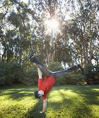 Hispanic man doing handstand outdoors