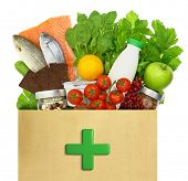 Paper bag with medical green cross filled with healthy foods