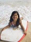 stock photo of boogie board  - Pacific Islander girl laying on boogie board - JPG
