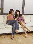 Multi-ethnic women sitting on sofa